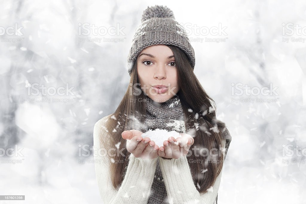 Winter portrait. Young, beautiful woman blowing snow stock photo