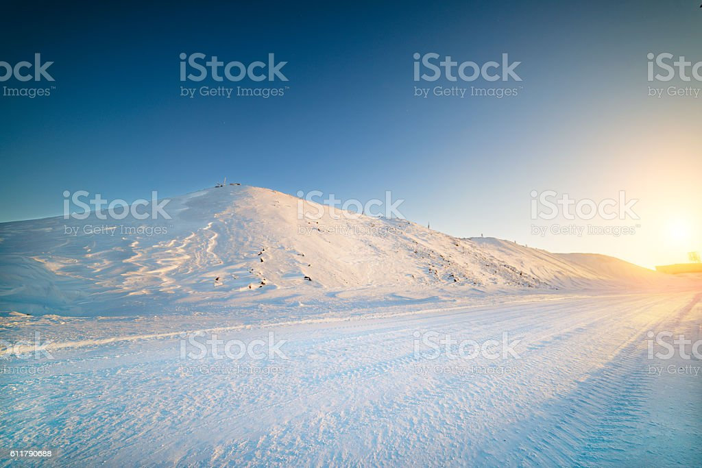 Winter road, among the snow-covered mountain slopes, the rising stock photo