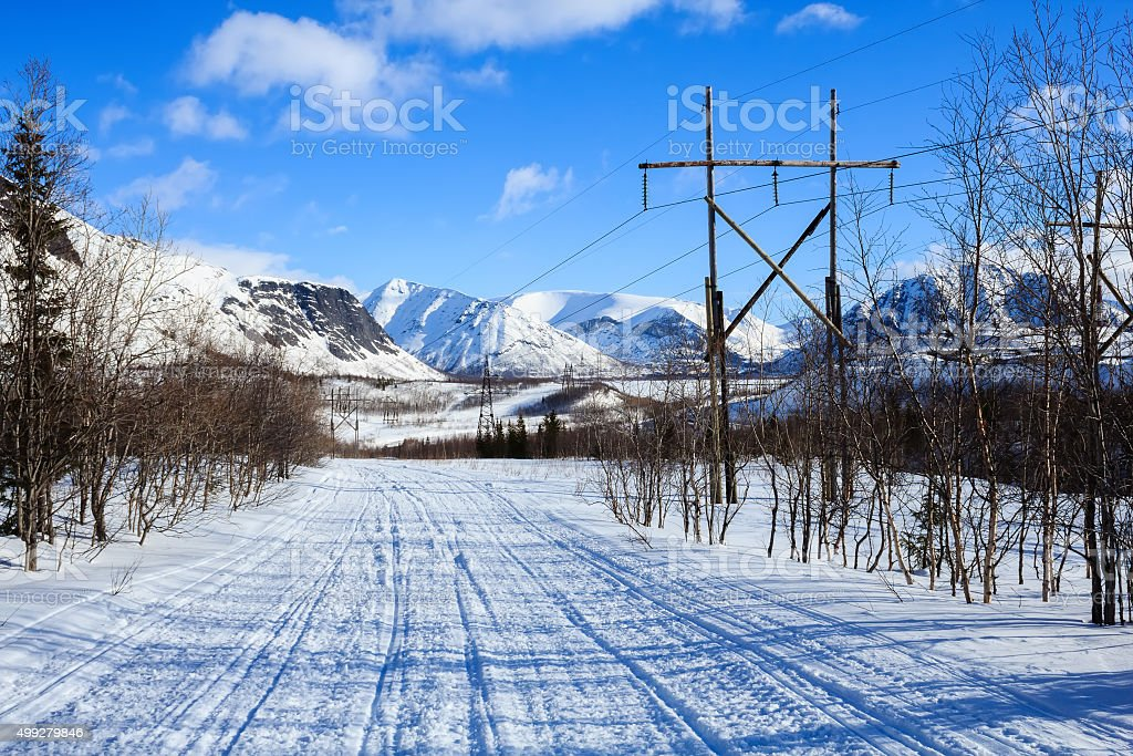 winter road in the polar mountains and old electricity pillars stock photo