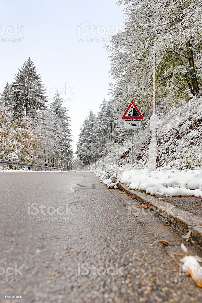 winter road with warning sign and bad weather royalty-free stock photo