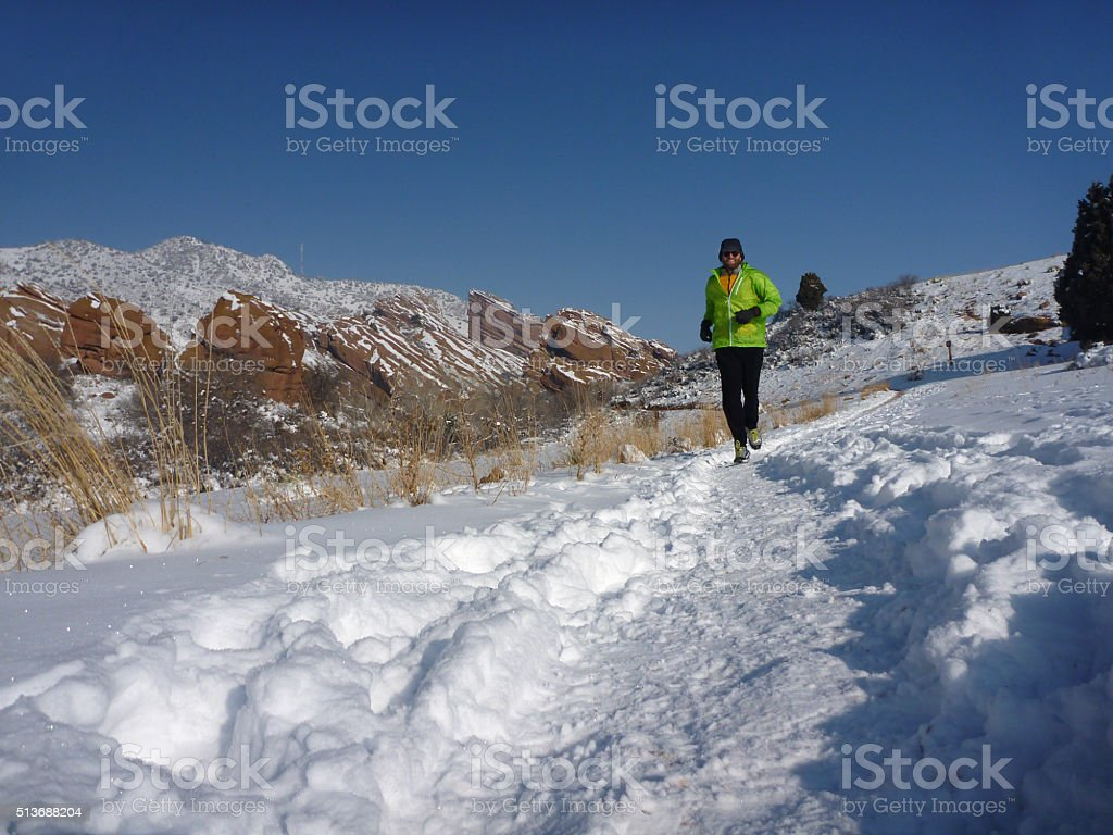 Winter runner in snow covered Red Rocks Park Colorado stock photo