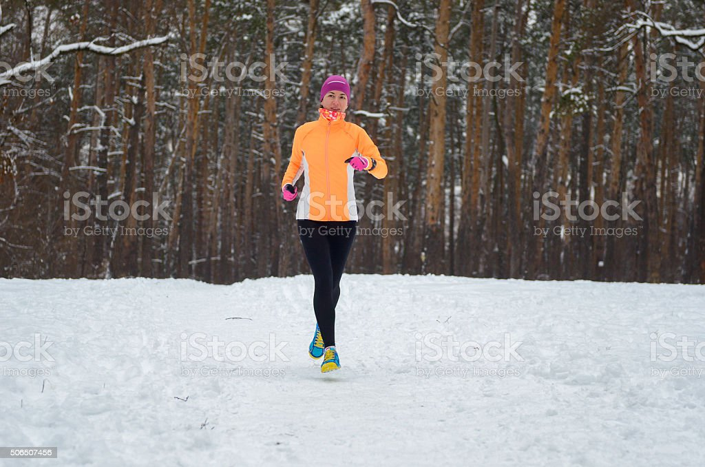 Winter running in forest: happy woman runner jogging in snow stock photo