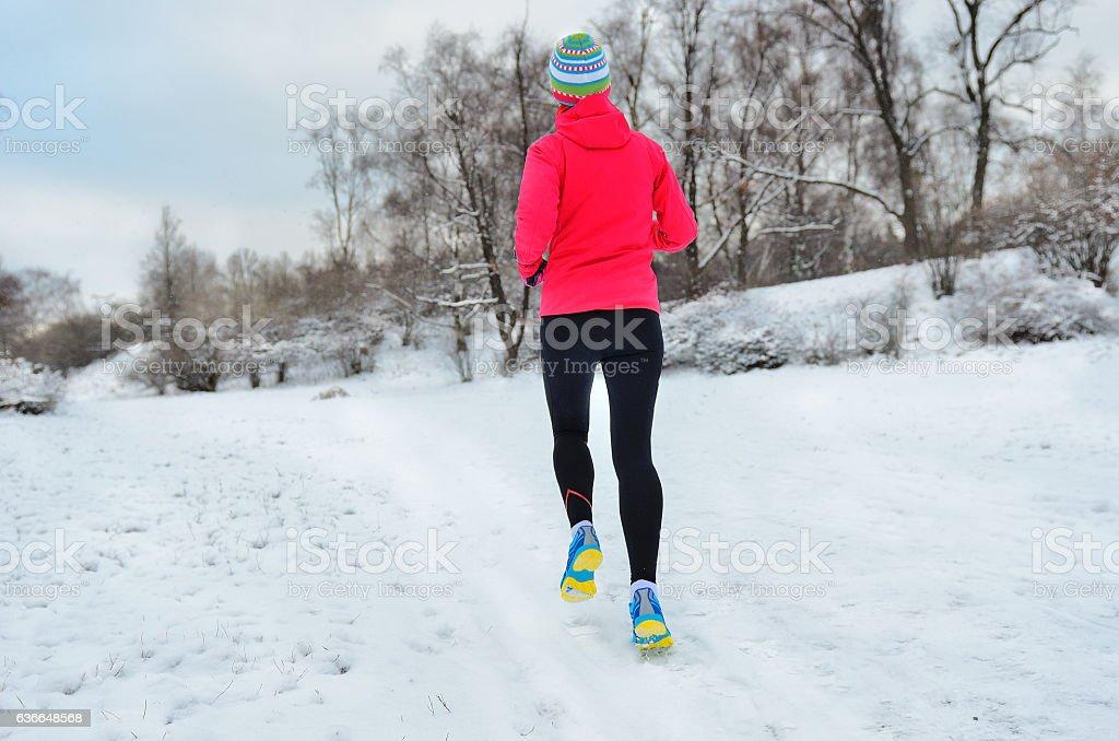 Winter running in park: happy woman runner jogging in snow stock photo