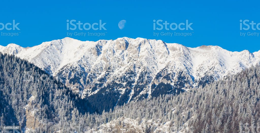 Winter scenery in the mountains, with snow covered peaks and setting moon stock photo