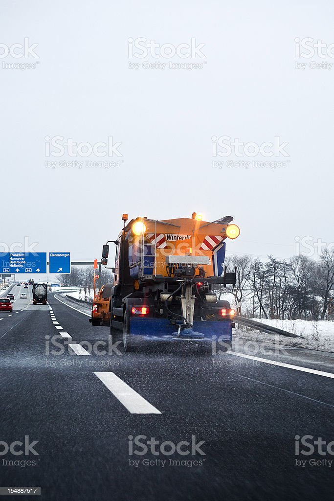 Winter service in action - laying road salt on autobahn royalty-free stock photo
