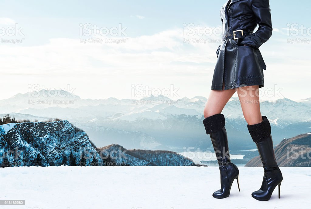 Winter shoes.Woman with black leather coat and boots in mountain. stock photo