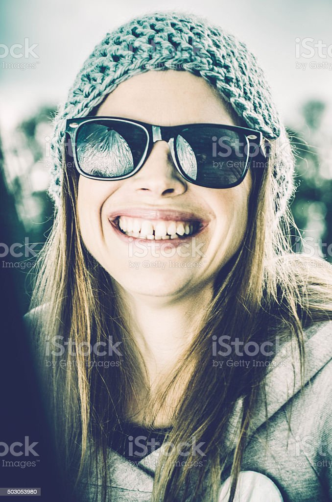 Winter smiling girl with a woolen hat and glasses stock photo