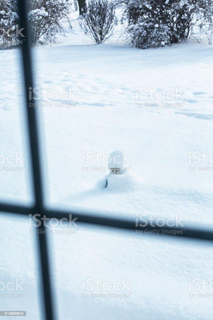 Winter Snow Capped Buried Garden Gnome Figurine stock photo