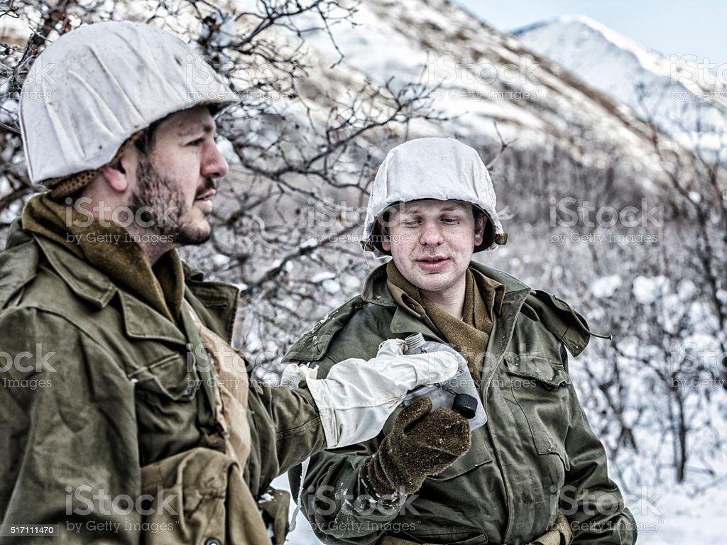 Winter Snow WWII US Army Soldiers Sharing Water Canteen stock photo