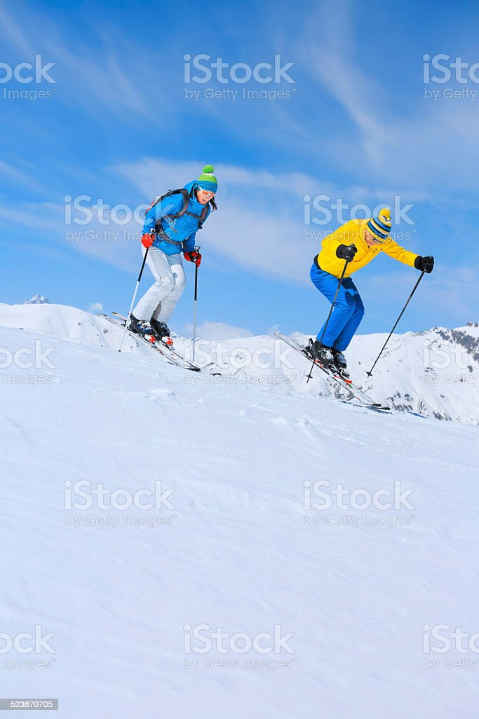 Winter sport, skiing couple jumping. Best friends men and women, snow...