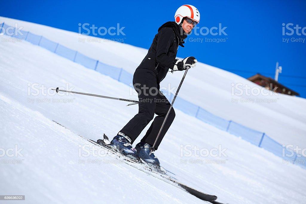 Winter sport. Mid adult women snow skier skiing, enjoying on sunny...