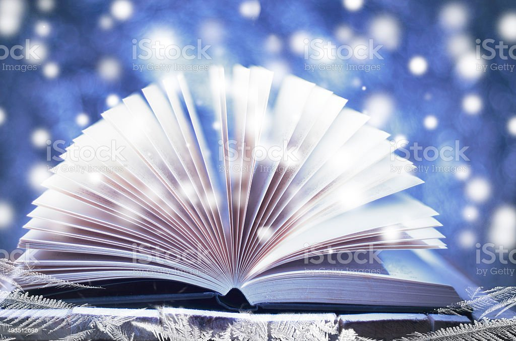 Winter story. Open book on wooden snowy blue background. stock photo
