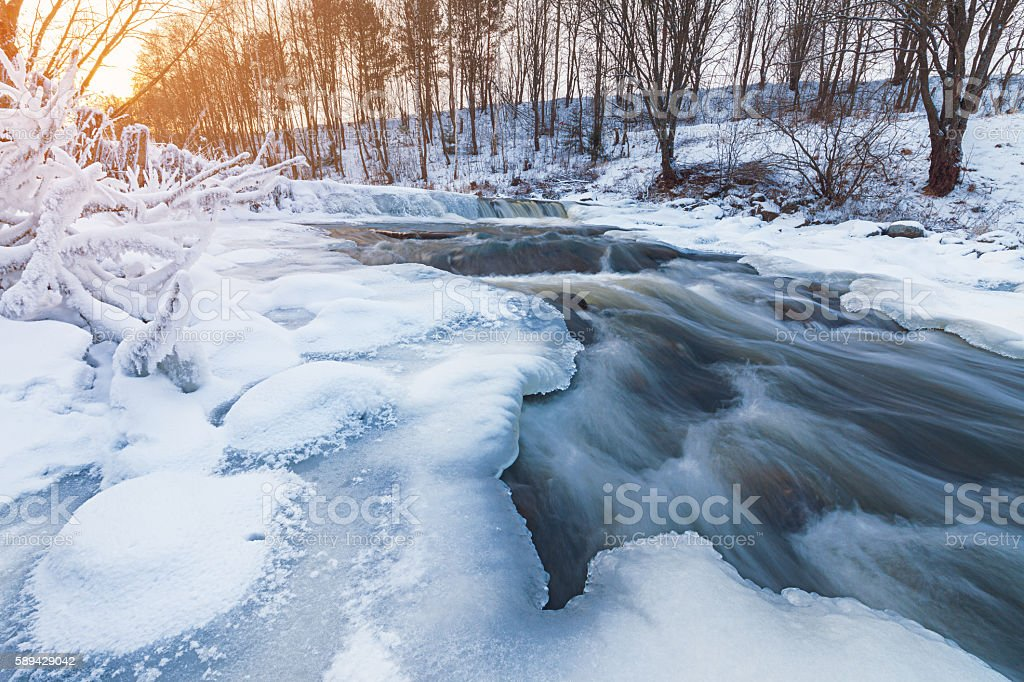 Winter stream at sunset stock photo