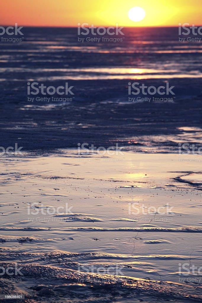 Winter sunset on the ice of Lake stock photo
