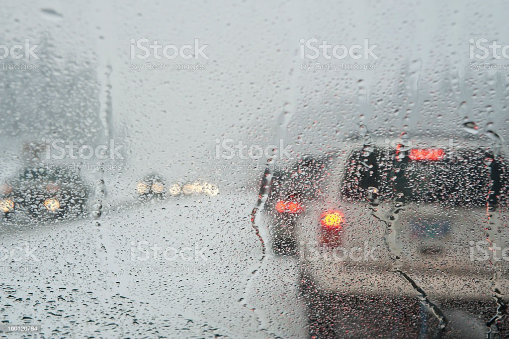 Winter traffic jam seen through a blurred, wet windshield stock photo