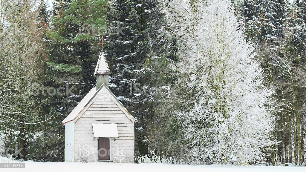 Winter view little snow-capped rural wooden church in frozen for stock photo