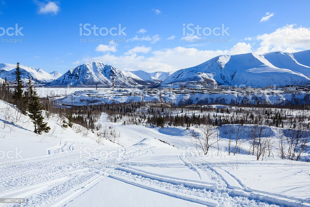 winter view of polar industrial city surrounded with snow mountains stock photo