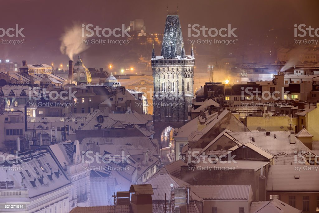 Winter view on Powder Gate and snowy rooftops at the Republic Square in Prague. In the distance you can see the National Monument in Vitkov. Old Town is a famous destination in Prague. Czech Republic stock photo