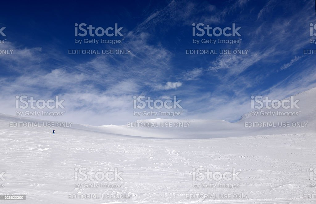 Winter white mountains and downhill skier stock photo