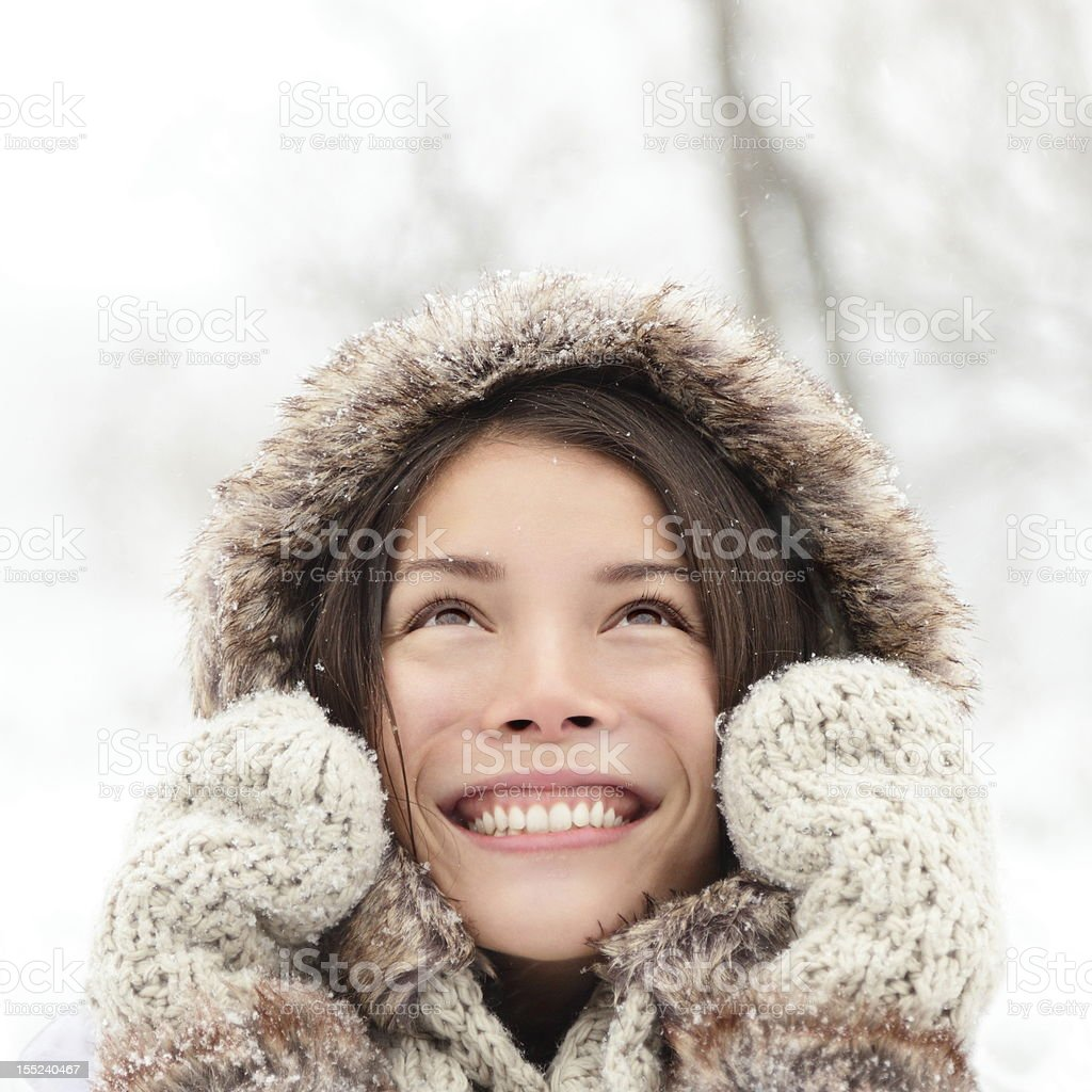 Winter woman looking up happy and smiling stock photo
