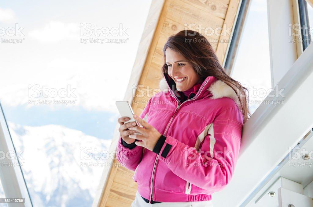 Winter woman using phone in lodge stock photo