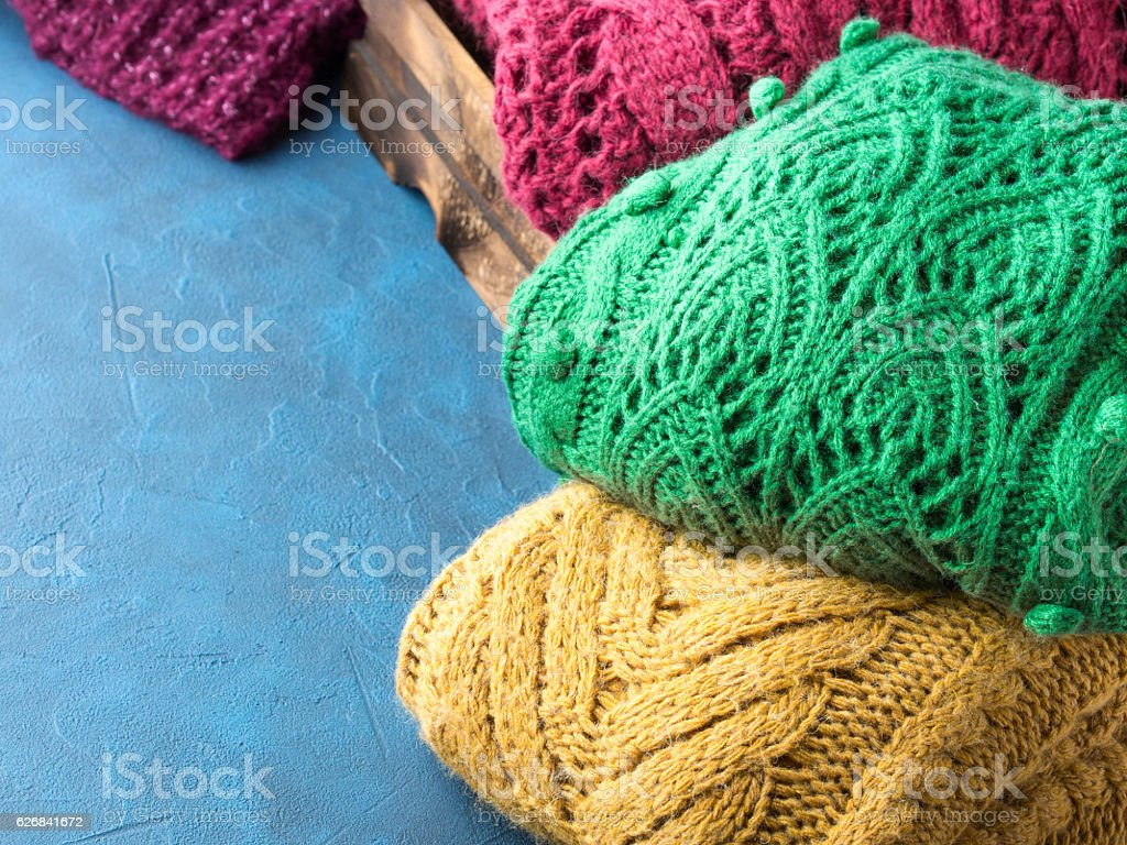 Winter womans woolen sweaters on blue background stock photo