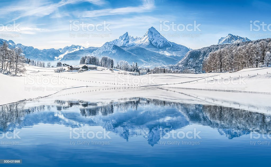 Winter wonderland in the Alps reflecting in crystal-clear mountain lake stock photo