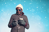 Winter young smiling african man listening music, smartphone, cup coffee