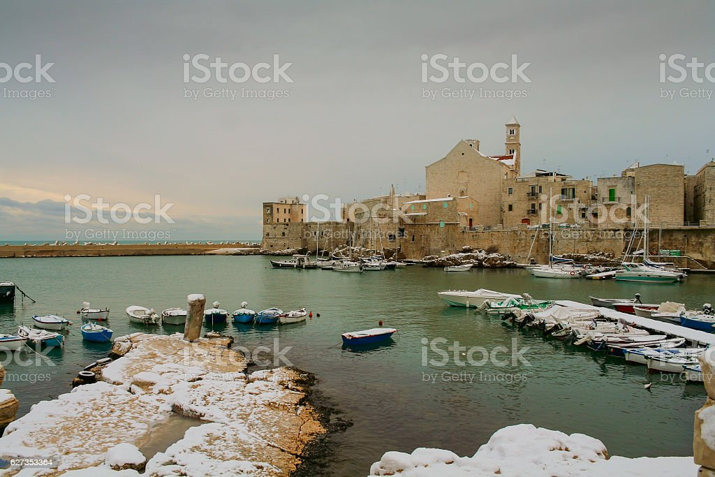 SEASCAPE WINTER.Giovinazzo's harbour:snowy cliff with docked boats.ITALY(Apulia) stock photo