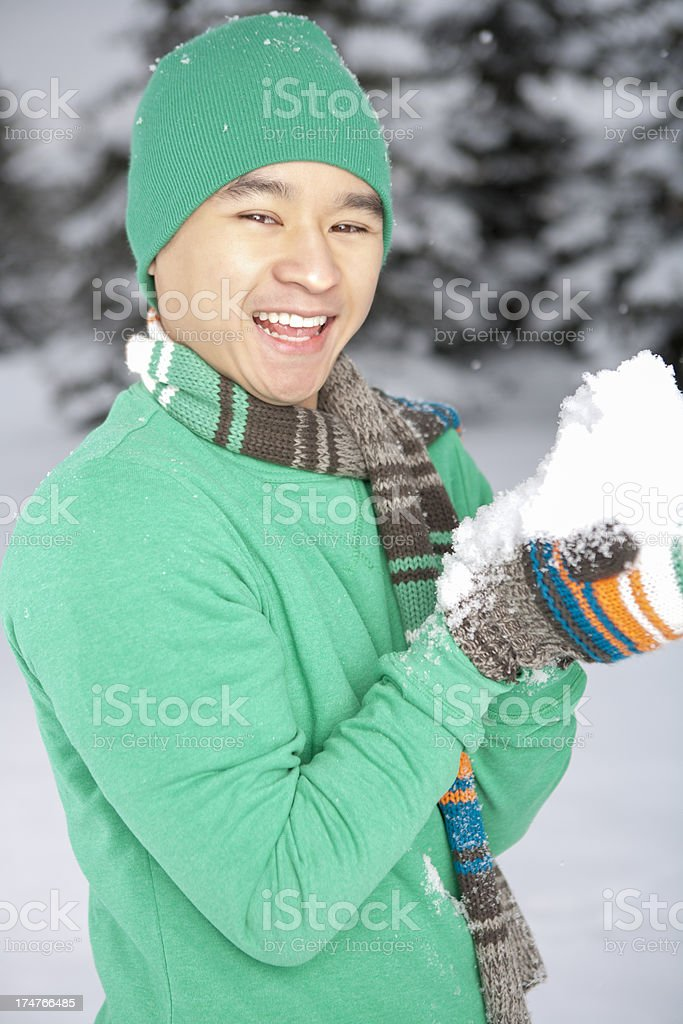 Winter-Smiling asian man playing with snow royalty-free stock photo