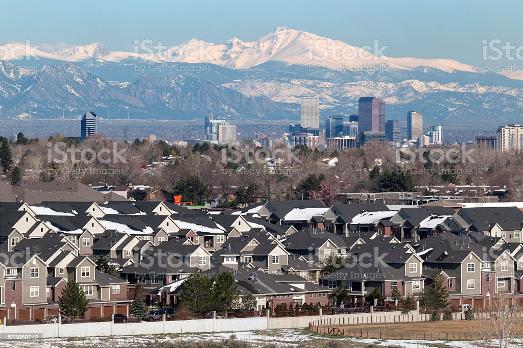 Wintery homes downtown Denver Colorado skyscrapers with Rocky Mountains stock photo