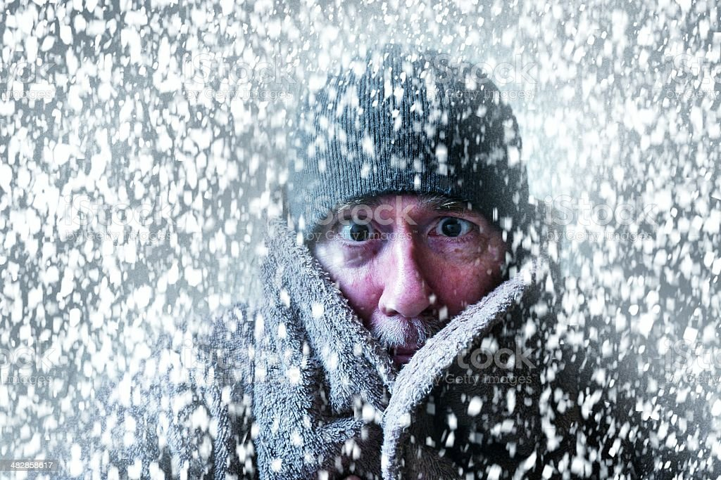 Wintery scene of a man shivering in a snow storm stock photo