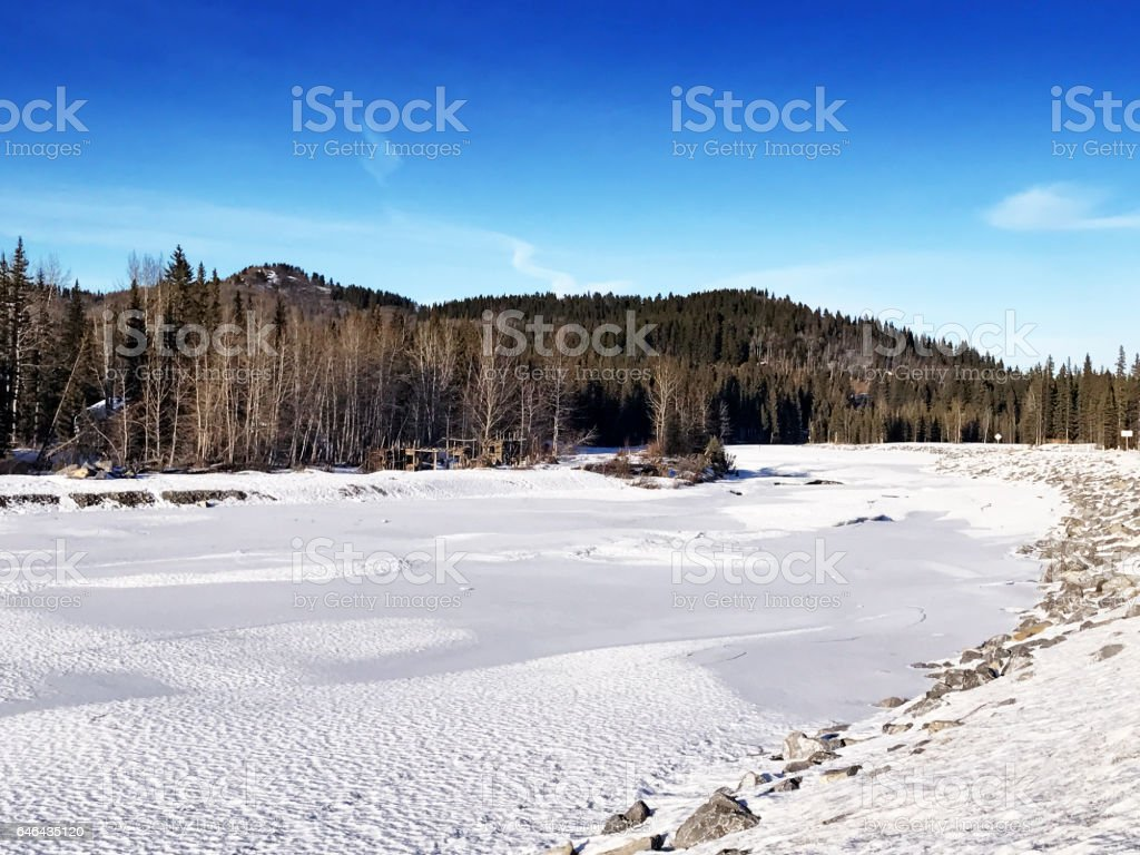 Wintry landscape with a frozen Elbow River in the hamlet of Bragg Creek,Alberta,Canada stock photo
