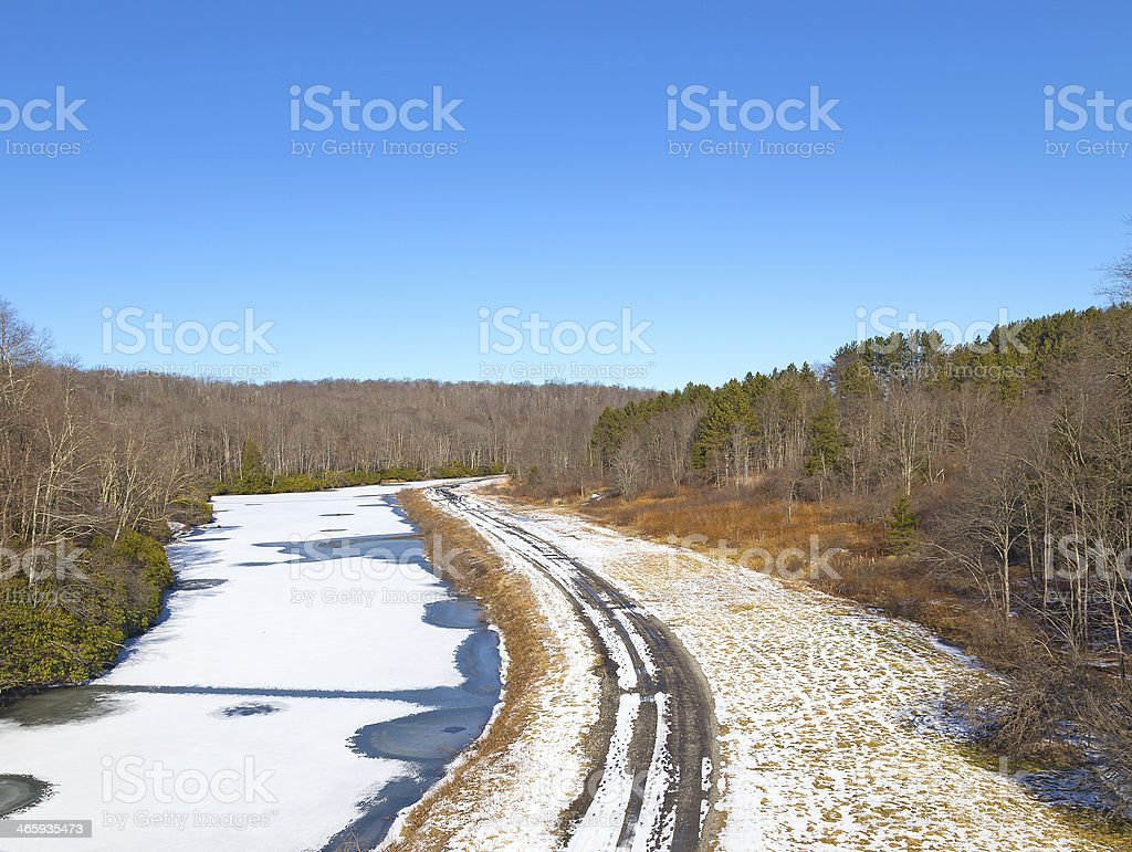 Wintry road running along the frozen river. stock photo