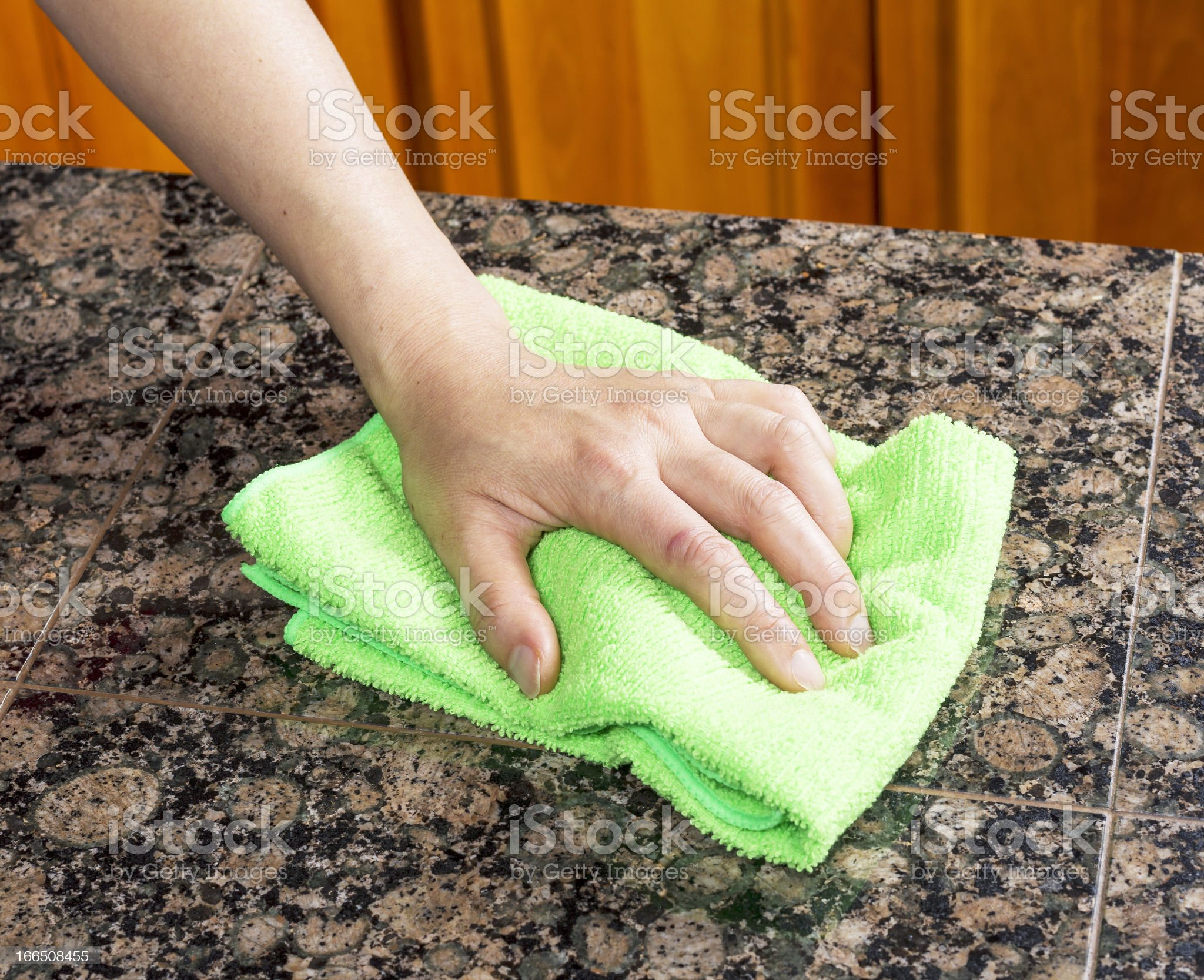 Wiping down Kitchen Stone Countertop royalty-free stock photo
