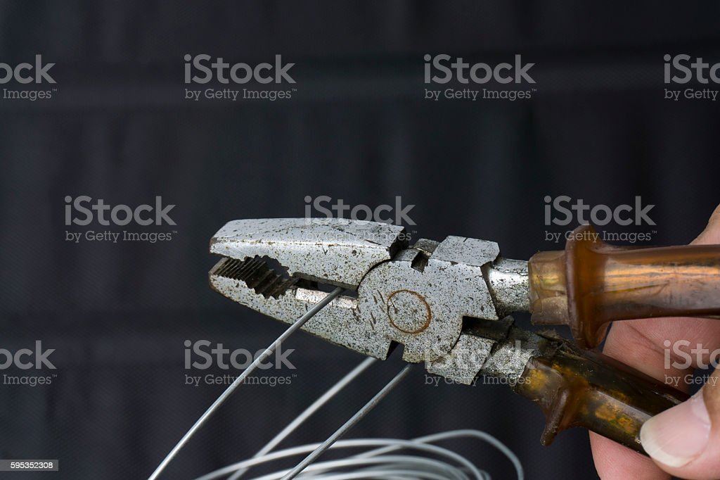 wire cutting with old pliers with dark background. stock photo