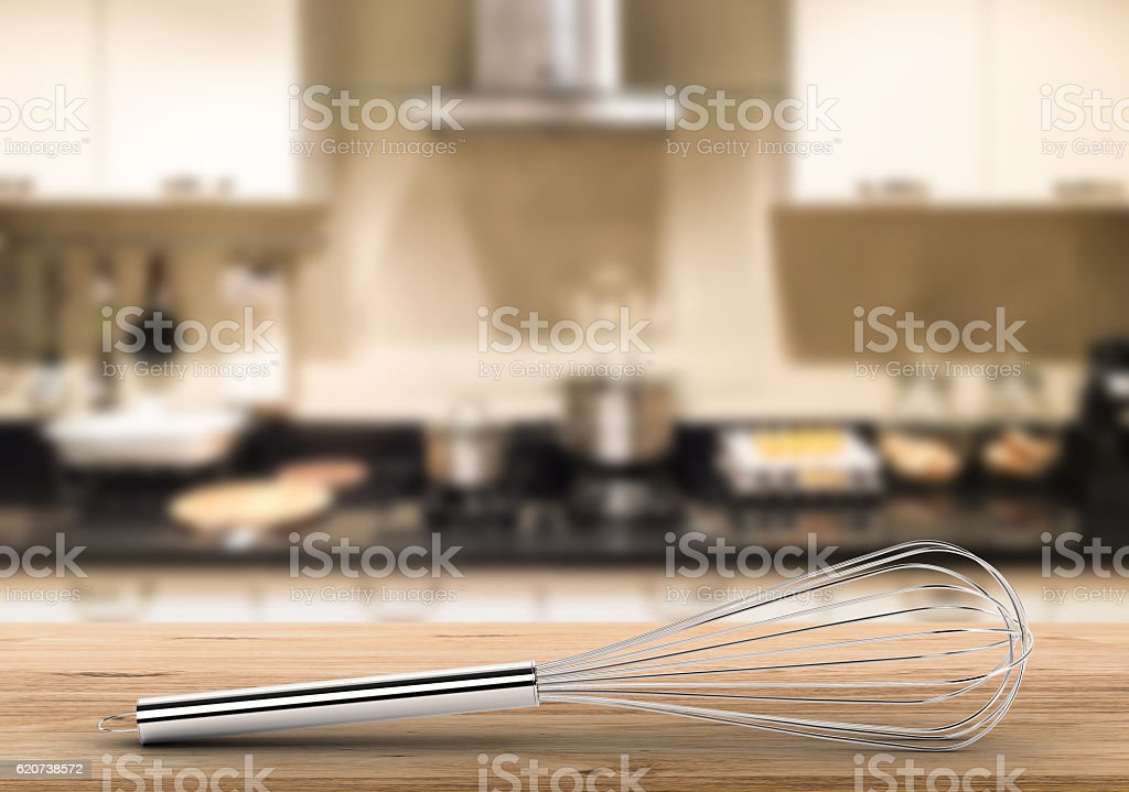 wire whisk on counter with kitchen background stock photo
