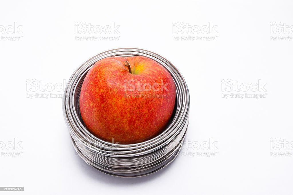 Wired apple: whole red apple in coils of wire isolated stock photo