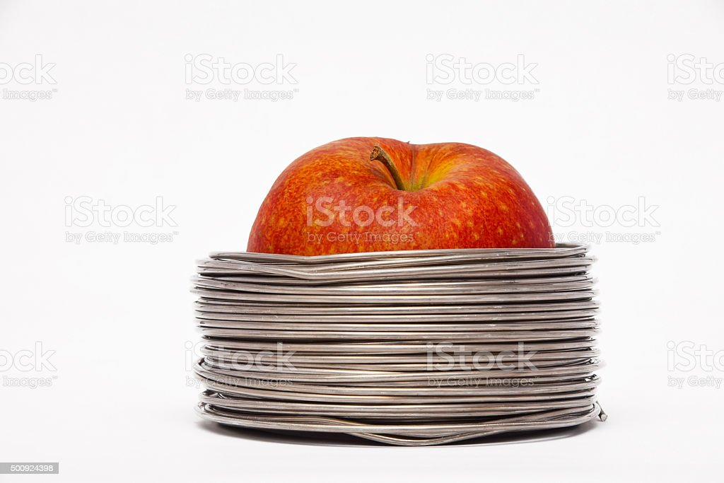 Wired apple: whole red apple in coils of wire isolated royalty-free stock photo