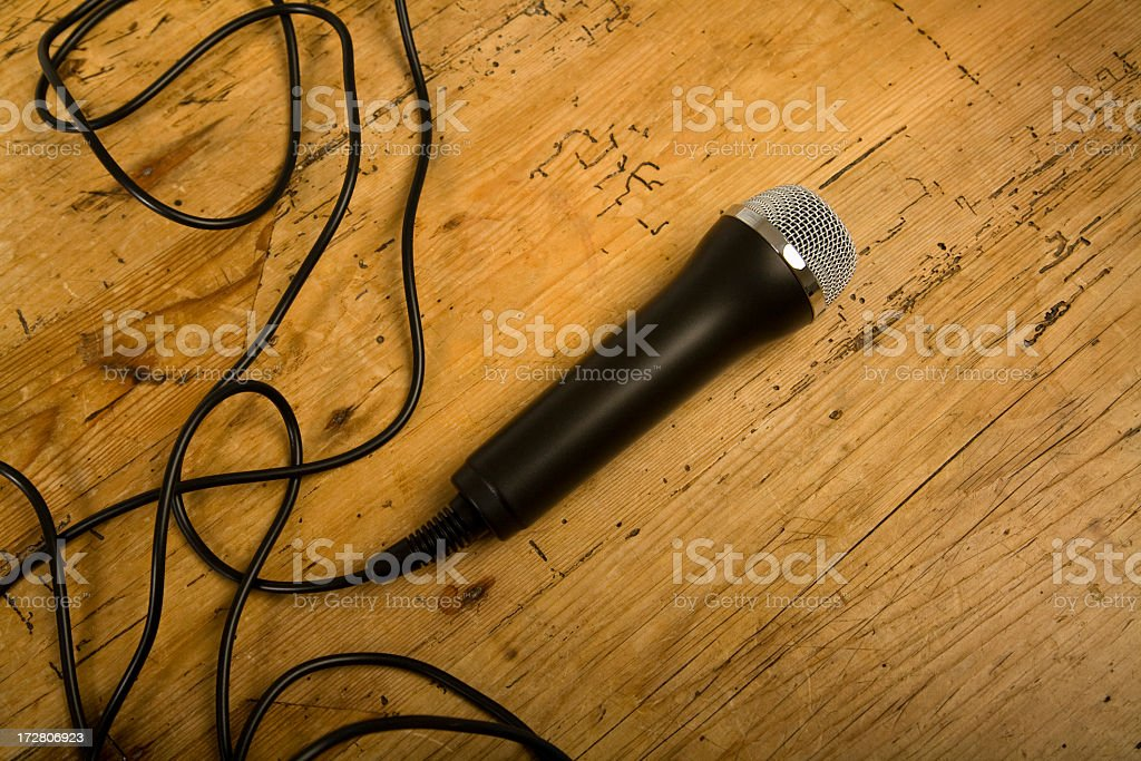 Wired microphone on wooden floor stock photo