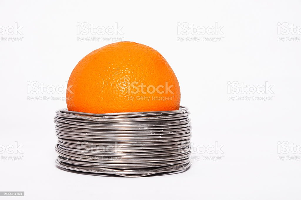 Wired orange: whole orange in coils of aluminium wire stock photo