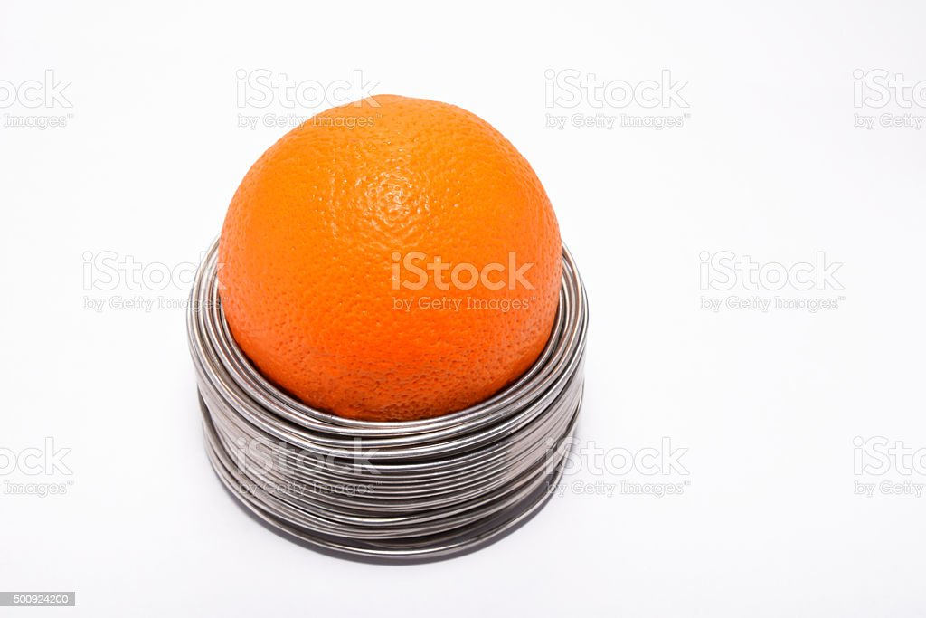 Wired orange: whole orange in coils of wire isolated royalty-free stock photo