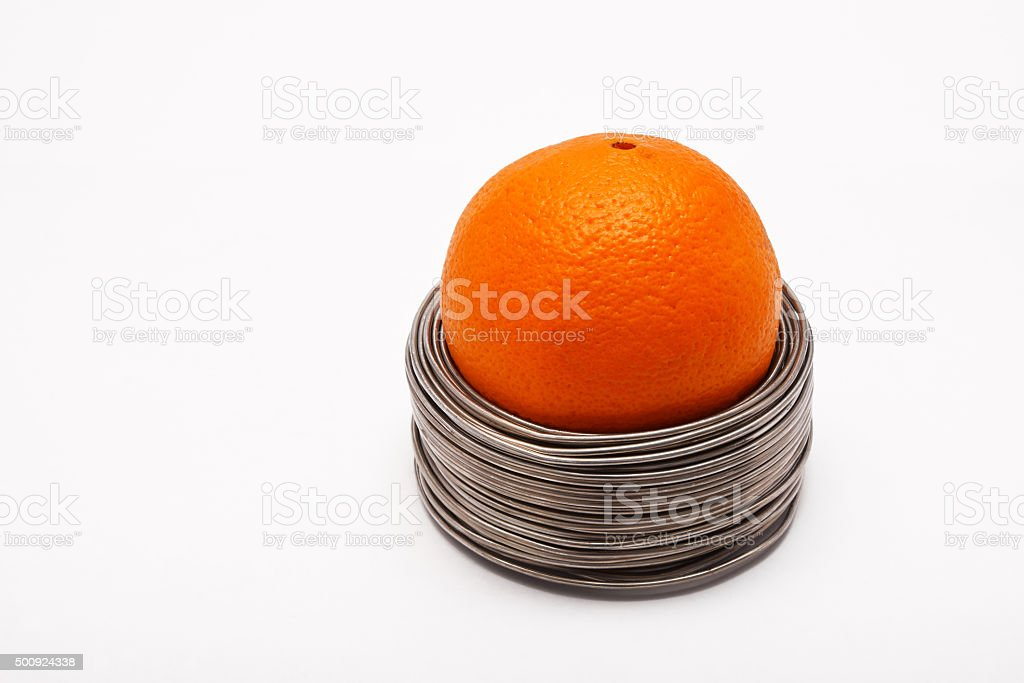 Wired orange: whole orange in coils of wire isolated stock photo