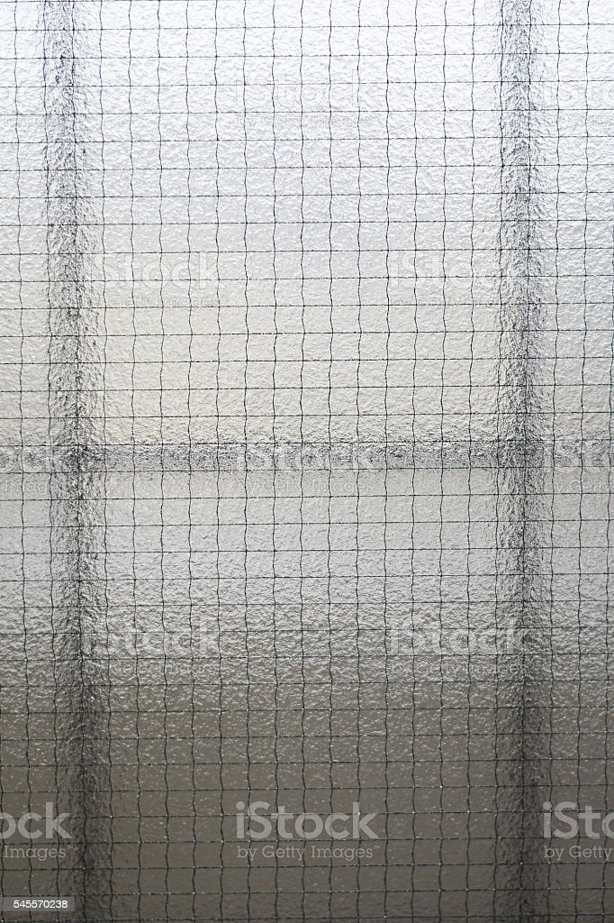 Wired reinforced pane of glass background stock photo