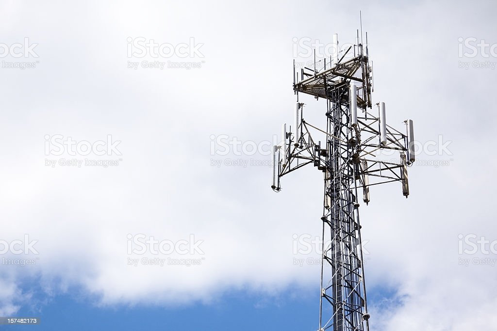 Wireless telecommunications repeater tower against lovely blue sky with clouds stock photo
