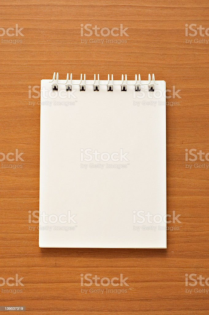 Wire-o notepad on wooden desk background royalty-free stock photo