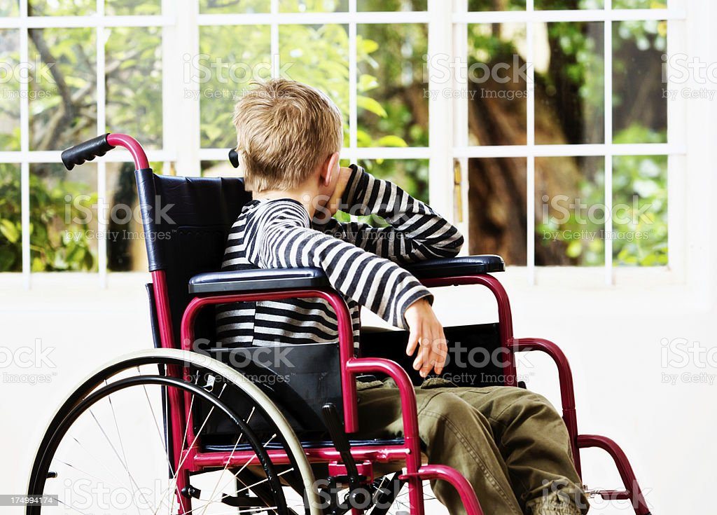 Wish I could play out there! Disabled boy watching garden stock photo