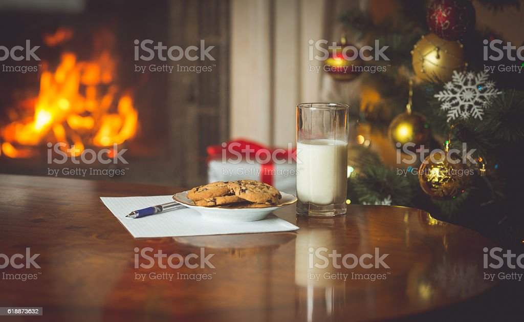 Wish list and treats for Santa on table at fireplace stock photo