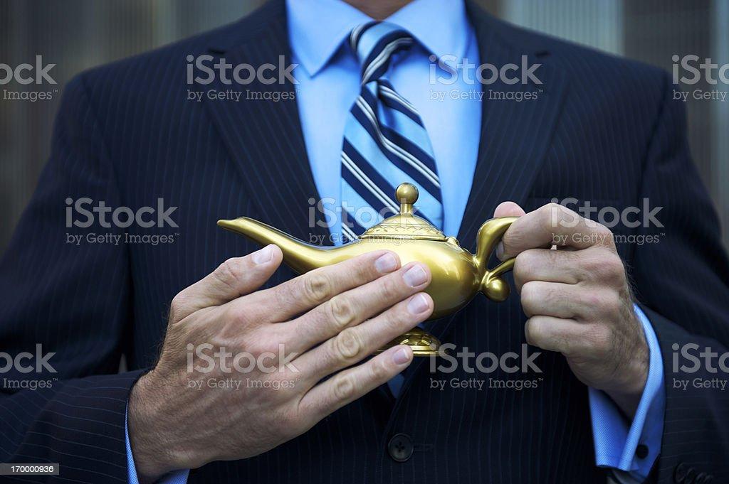 Wishing Businessman Rubbing Golden Magic Lamp with Three Wishes stock photo