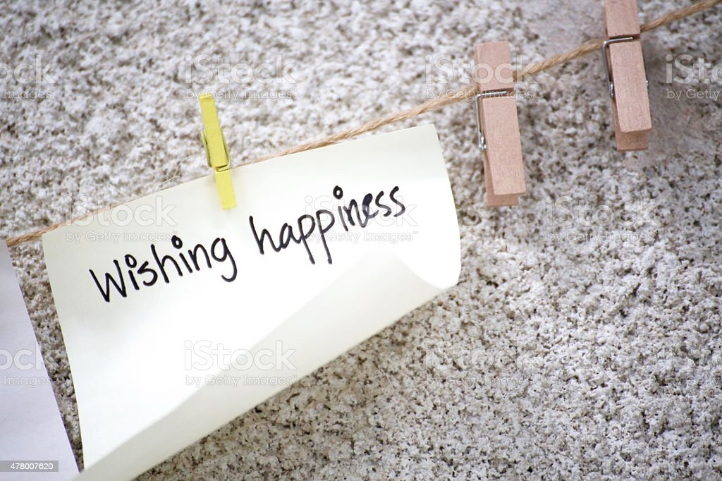 Wishing happiness note hang on the wall stock photo
